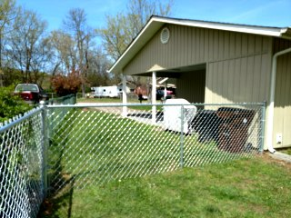 chain link fence behind yellow house with carport