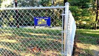 chain link fence with blue and yellow sign on it