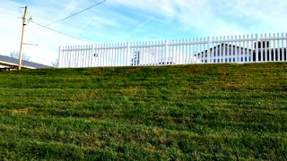 picket fence on grassy hill