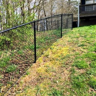 black chain link fence going up hill in a yard with yellow and green grass