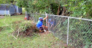 person doing repairs on a chain link fence near brush and a blue house