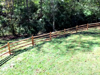 rail fence going down a hill near trees and green grass
