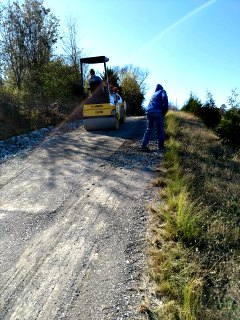 people working on a gravel road with a yellow machine on a grassy hillside