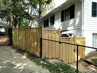 fence with lattice on top near a house with black shutters and black chain link fence