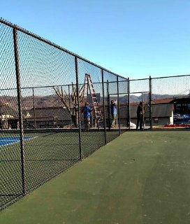 people working on tennis court fence near a tall ladder